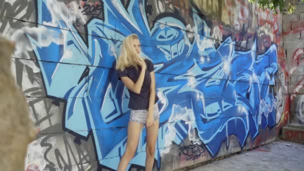 Fiatal szőke lány pózol a háttérben a fal grafitti. Videó-munkamenet. lassított mozgás