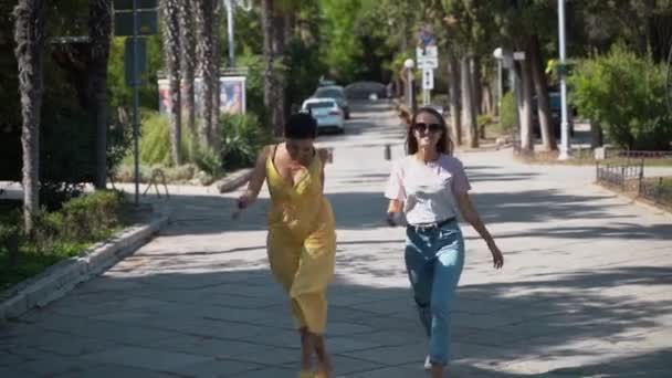 Two young girls joyfully run along the road