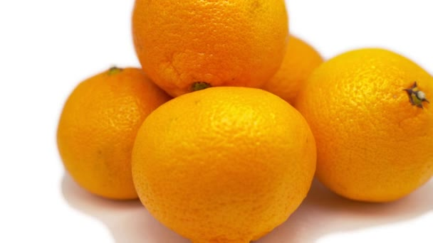 Five tangerines rotate on a white background. One mandarin lies on top of the other mandarins. Close-up