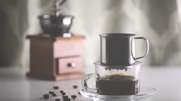 Antique kávu filtru filtrované kávy se nalije do čirého skla se kávová zrna a mlýnek na kávu na bílém stole