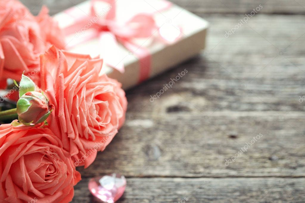 Delicate coral shade pink roses and gift with heart and letterhead on rustic wooden background. Valentine background. Holiday card for women