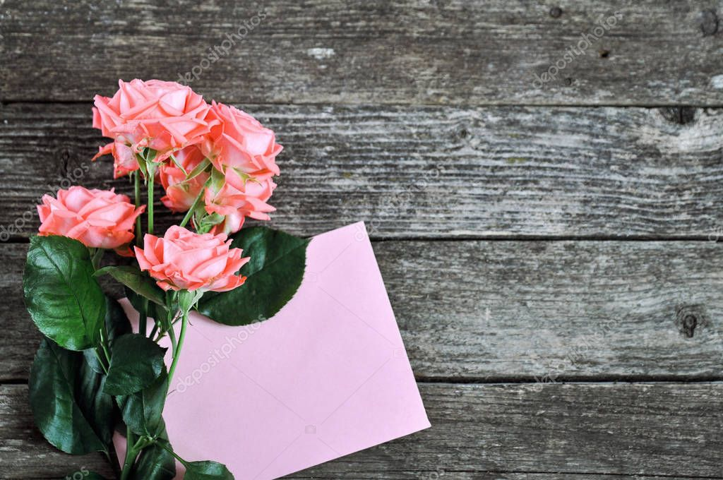 Delicate coral shade pink roses and letterhead on rustic wooden background. Valentine background. Holiday card for women. close up. selective focus