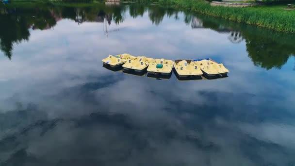 Pohled na jezero, které odráží oblačlivou oblohu, a na něm vznášedé žluté čluny. 4k.
