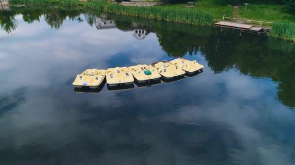 Letecký pohled na krásné jezero s lodičky, které kolem něj odrážejí úžasný ráz. 4k.