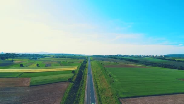 Letecký pohled, který pomalu snižuje zaměření na obrovské náklaďáky na cinematické cestě, ležící v úžasné krajině. 4k.