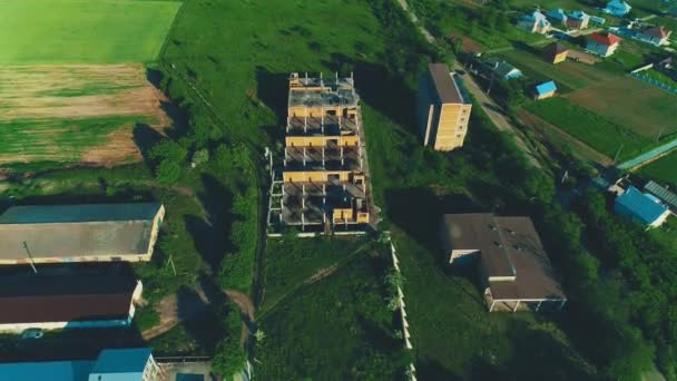 Aerial view of construction of residential buildings in rural area whithin scenic nature. 4K.