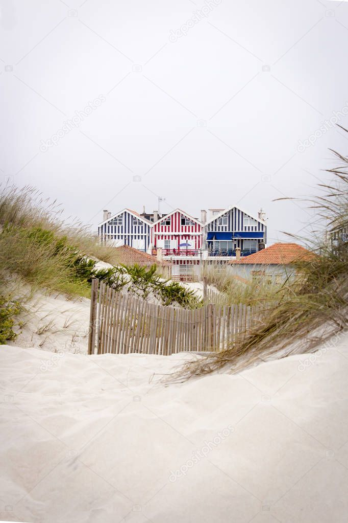 Lovely and quaint beach houses seen from beach dunes. Beach houses with colorful stripes from Costa Nova, Portugal.