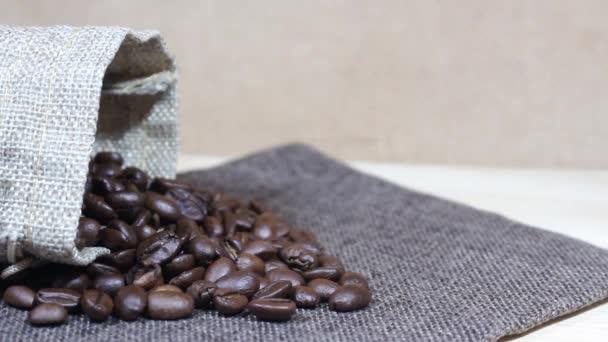 geröstete Kaffeebohnen, die in einen Stapel Kaffeebohnen neben einem Sack mit Klecksen fallen.