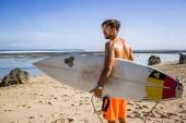 boční pohled mladý surfař s surfování stojí na písečné pláži v letním dni