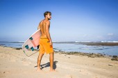 Fotografie young surfer with surfing board standing on sandy beach on summer day