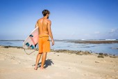 Fotografie rear view of surfer with surfing board standing on sandy beach on summer day
