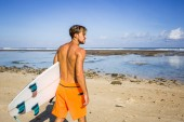 Fotografie back view of surfer with surfing board standing on sandy beach on summer day