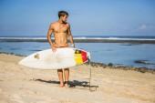mladý muž s Radou surfování na písečné pláži v blízkosti oceánu