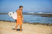Fotografie mladý muž s Radou surfování na písečné pláži v blízkosti oceánu