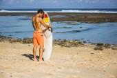 Fotografie surfer putting surf board into sand on beach