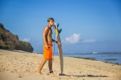 Fotografie side view of young man with surfing board on sandy beach near ocean