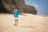 Fotografie back view of sportsman walking on beach, Bali, Indonesia