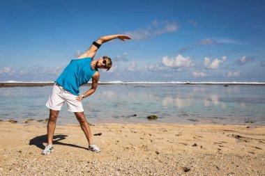 athletic man in sportswear stretching on beach near sea
