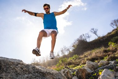 Bottom view of athletic man jumping from rocks with sunlight stock vector