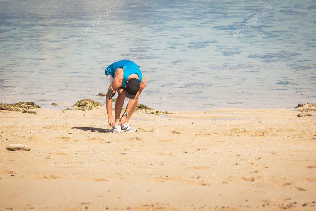 sportsman with smartphone armband tying shoelaces on beach near the sea