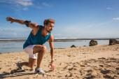 Photo athletic man with armband doing lunges during workout on seashore
