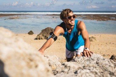 smiling sportsman climbing on rocks on beach, Bali, Indonesia