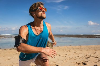 sportsman listening music with smartphone armband while doing lunges on beach