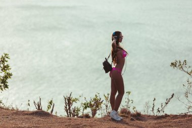 Side view of attractive girl in headphones and pink bikini standing on coastline stock vector