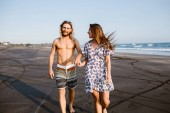 Photo smiling couple holding hands and walking on beach in bali, indonesia