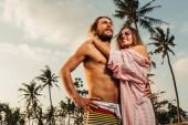 nízký úhel pohled přítel a přítelkyně objímání na pláži v bali, Indonésie