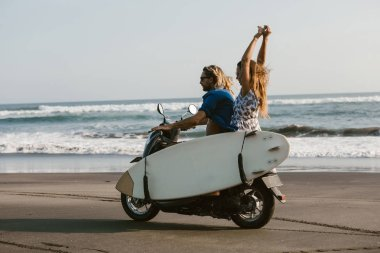 side view of couple riding scooter with surfboard on beach in bali, indonesia