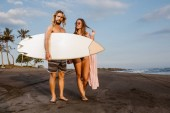 Photo couple standing with surfboard on beach in bali, indonesia