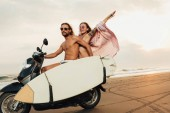 Photo couple riding motorbike with surfboard on beach in bali, indonesia