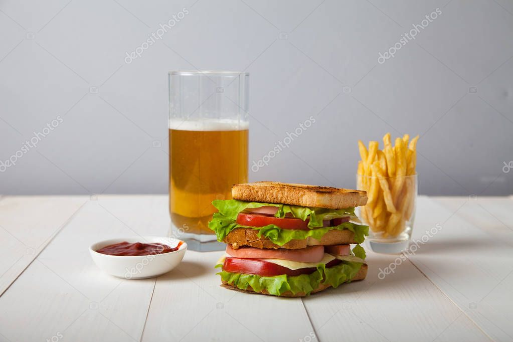 sandwich with beer, fried potatoes and sauce on a white wooden t