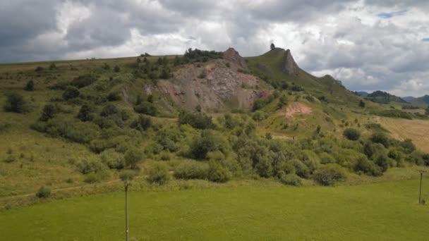 létání nad kopec (kamenů a trávy) letecké záběry hill, trávy, skály a stromy, pak krásný výhled otevře za kopcem: louky, pole, hory, lesy a ve vzdálenosti stádo ovcí