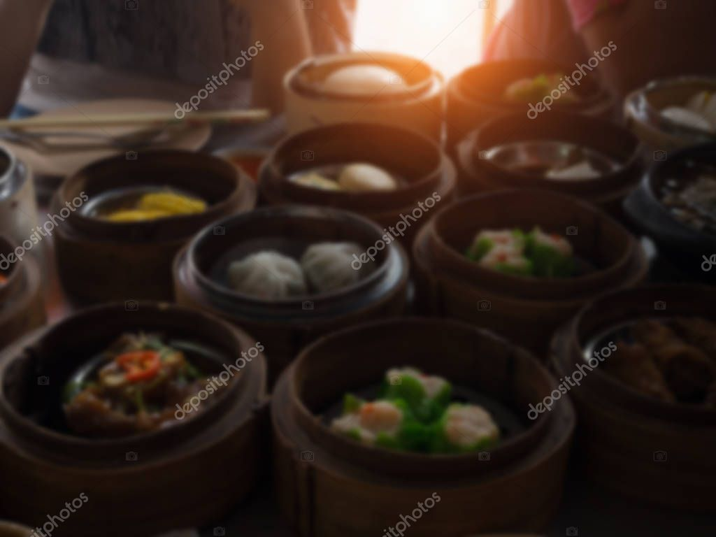 The blurry light design background of Chinese food ,Dimsum in bamboo basket.put on table,at  chinese food reataurant.