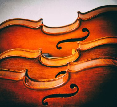 The abstract art design background of violins stacked on board,show half front side of violin,in dramatic tone, vintage and art style,blurry light around.