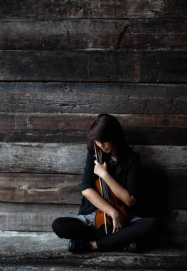 The lady is sitting on grunge surface cement floor,hold violin and bow in her arms,turn face down to volin,vintage and art style,blurry light around.