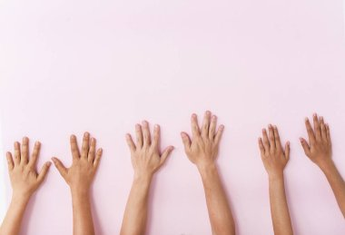 The human hands touch on pink pastel background,the hand sign of togetherness,partnership of human,union,the symbol of successful and cheerful