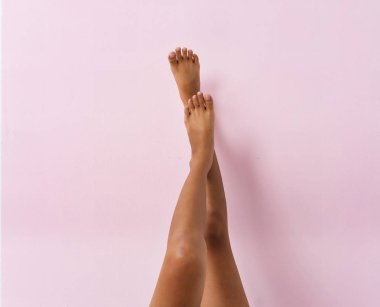 The left leg put on right leg,pink pastel background,show beauty body of lady