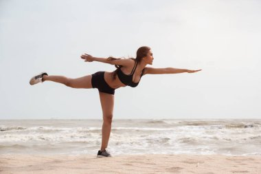 lady with sportwear is stand with left leg side and raise right leg up in the air,raise left hand up in the air and bend like arrow ,posing yoga pattern on the beach