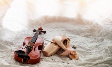 The wooden violin put beside ballet shoes,on background,warm light tone,blurry light design background