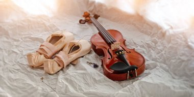 The ballet shoes and violin put on background,warm light tone,blurry light around.