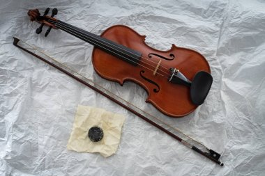 The wooden violin put beside bow and rosin,on background,prepare for practice