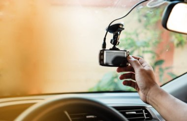 The human hand is touching the CCTV car camera,for check system before use,the technology for car user,for safe and secure driving,warm light tone,blurry light around