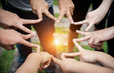 The human fingers touching together,sign and symbol of fighting and power of team,teamwork concept,blurry light around
