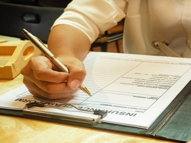 The human hand is filling information on the insurance claim form,