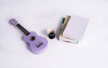 Coffee cup put at the middle of Ukulele and books stacked,on white background