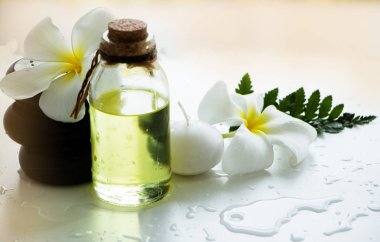 The aromagheraphy massage oil put beside black rock spa ,candle and flower, spa therapy on background