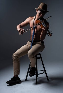 Thw handsome man show body muscle ,sitting on black chair,playing violin with happy feeling,vintage and art tone